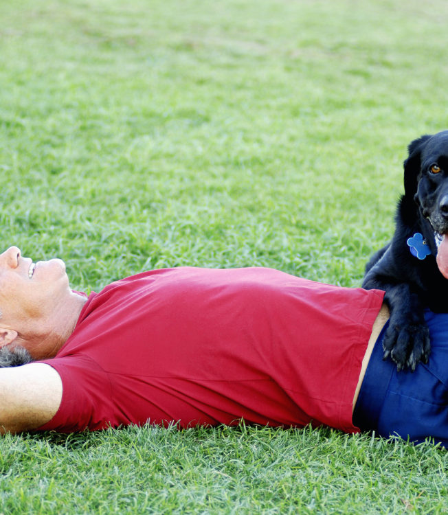 A pet owner lying in grass with his black dog - SRVC